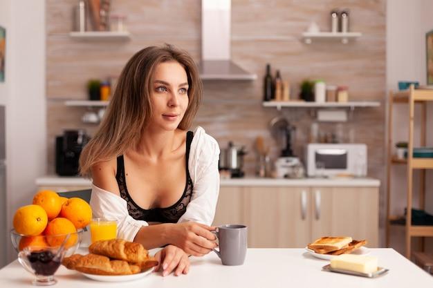 Vrouw die lacht naar de camera tijdens het ontbijt, gekleed in verleidelijke zwarte lingerie jonge sexy verleidelijke blode...