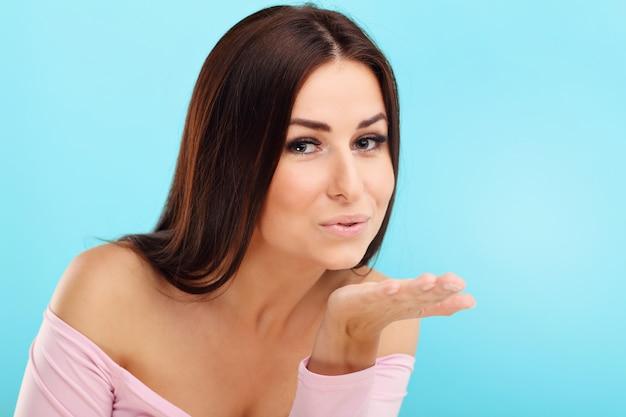 Vrouw die lacht tegen blauwe achtergrond