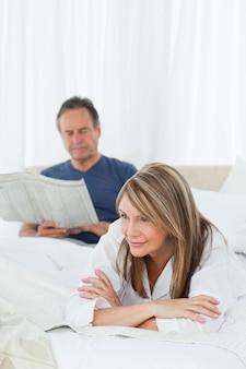 Vrouw die lacht terwijl haar man aan het lezen is