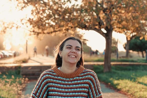 Vrouw die lacht tijdens een zonsondergang in een park
