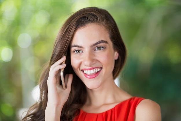 Vrouw die lacht tijdens het praten op haar mobiele telefoon