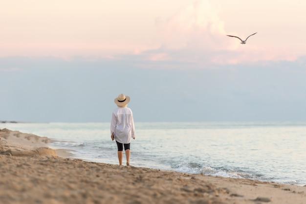 Vrouw die langs strand bij de celtelefoon van de zonsondergangholding loopt en strohoed en het dromen draagt