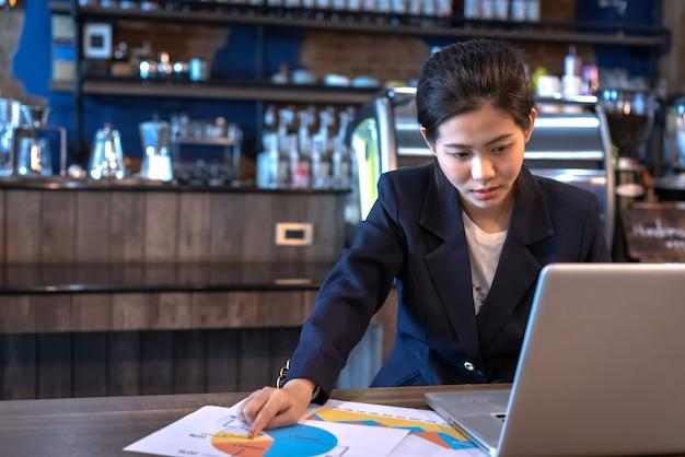 Vrouw die laptop en millimeterpapier met energetisch in koffiewinkel bekijken