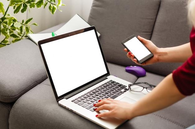 Vrouw die laptop en smartphone in koffie gebruiken