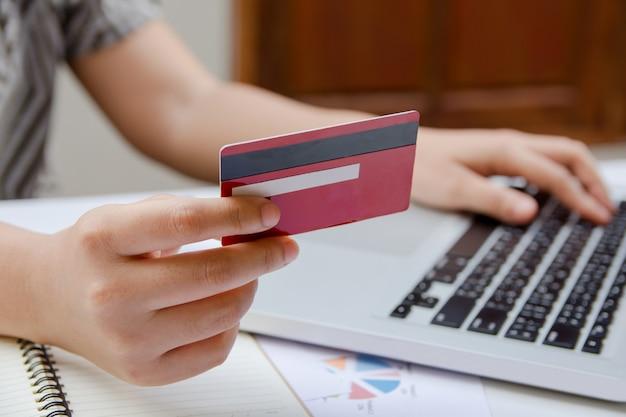 Vrouw die laptop gebruikt en creditcard met online online het winkelen of internet-bankwezen houdt.