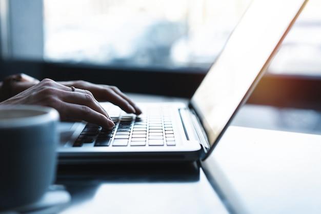 Vrouw die laptop gebruikt, op internet zoekt, informatie doorbladert, een werkplek heeft thuis of in een creatief kantoor of café.