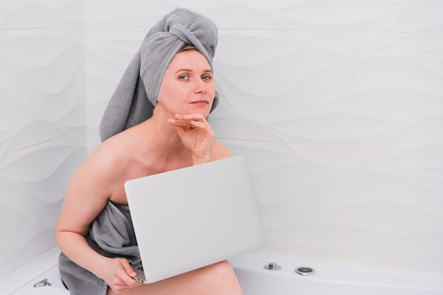 Vrouw die laptop in badkuip houdt