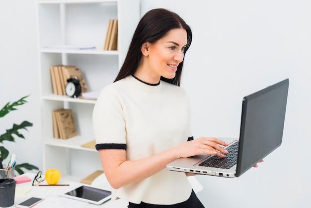 Vrouw die laptop in bureau met behulp van