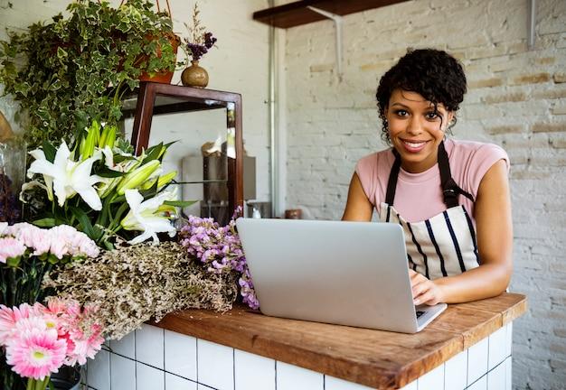 Vrouw die laptop online bloemwinkel gebruikt