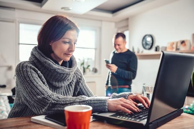 Vrouw die laptop thuis kantoor met behulp van