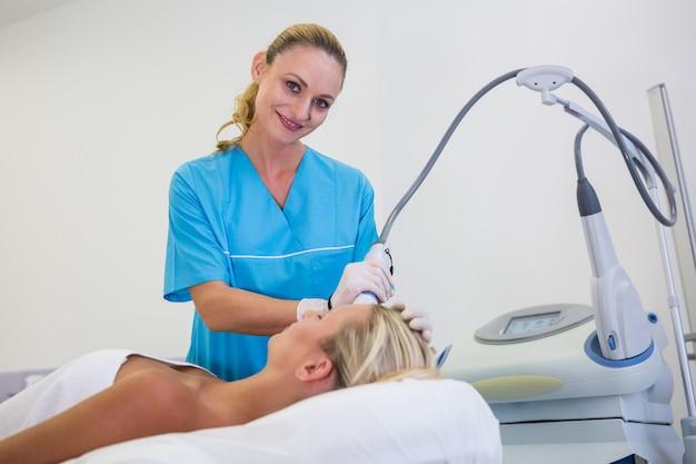 Vrouw die laser epilatiebehandeling op haar voorhoofd ontvangt