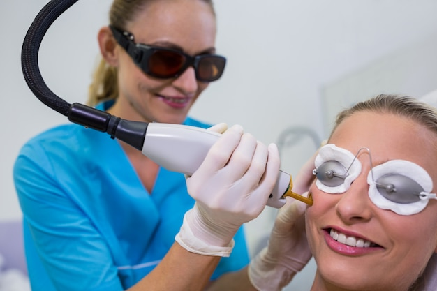 Vrouw die laserepilatiebehandeling op haar gezicht ontvangt