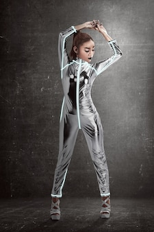 Vrouw die latex jumpsuit het stellen over grungeachtergrond draagt