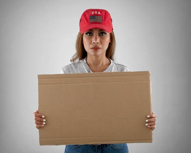 Vrouw die leeg aanplakbiljet middelgroot schot houdt