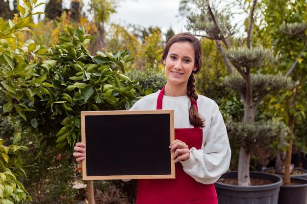 Vrouw die leeg bord in tuin houdt