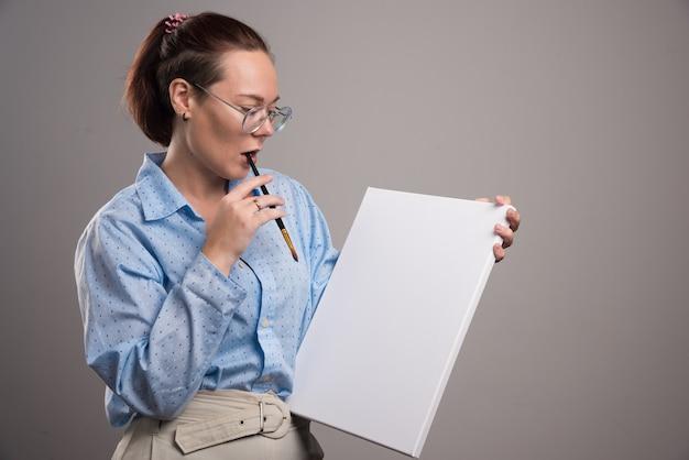 Vrouw die leeg canvas en penseel op grijze achtergrond bekijkt