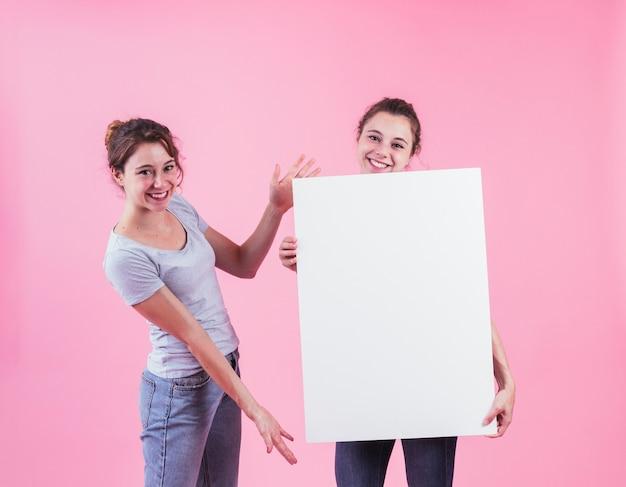 Vrouw die lege aanplakbiljetholding voorstellen door haar vriend tegen roze achtergrond