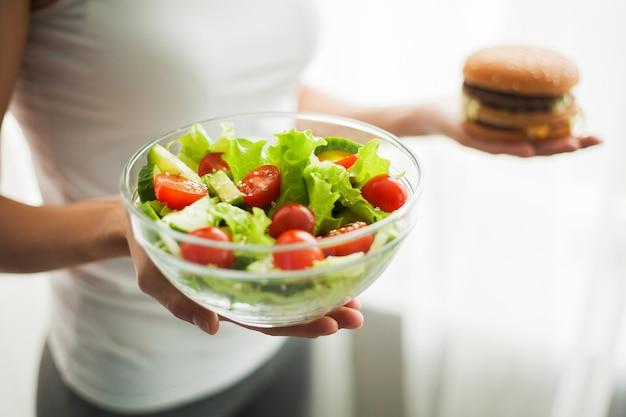 Vrouw die lichaamsgewicht op weegschaal meten hamburger en salat houden.