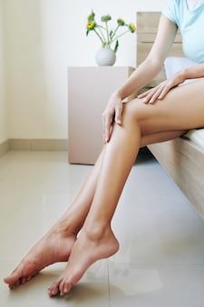 Vrouw die lichaamsvochtinbrengende crème toepast