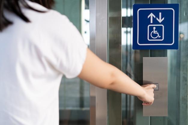Vrouw die lift voor gehandicaptenmensen in het gebouw gebruiken