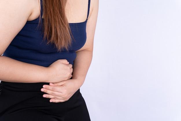 Vrouw die lijdt aan maagpijn en letsel geïsoleerd grijze achtergrond.