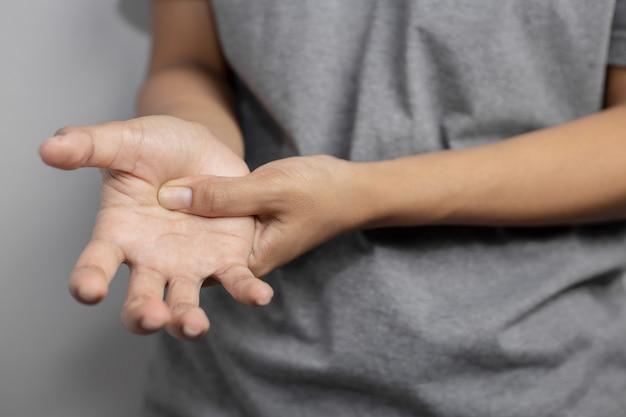 Vrouw die lijdt aan pijn in de hand. pijn in de hand. jonge vrouw houdt pijn van de hand.
