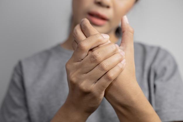 Vrouw die lijdt aan pijn in de hand.