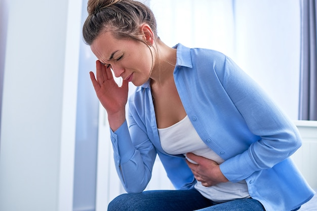 Vrouw die lijdt aan sterke spasmen, buikpijn tijdens maagzweren