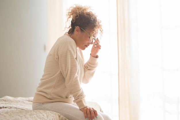 Vrouw die lijdt aan stress of hoofdpijn die 's ochtends op het bed in de slaapkamer zit met een grimas van de pijn
