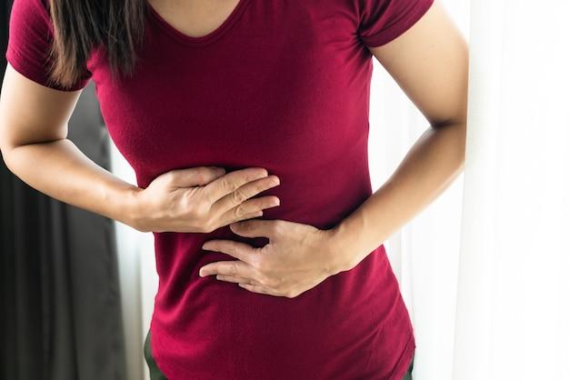 Vrouw die lijdt aan zure reflux of gastro-oesofageale reflux thuis