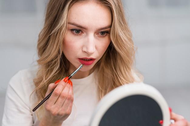 Vrouw die lippenmake-up met spiegel doet