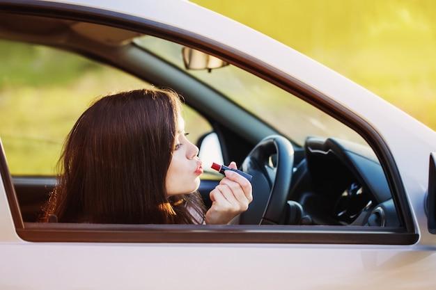 Vrouw die lippenstift in de auto zet vóór datum