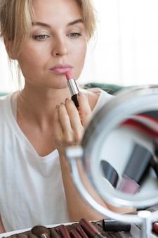 Vrouw die lippenstift in de spiegel toepast