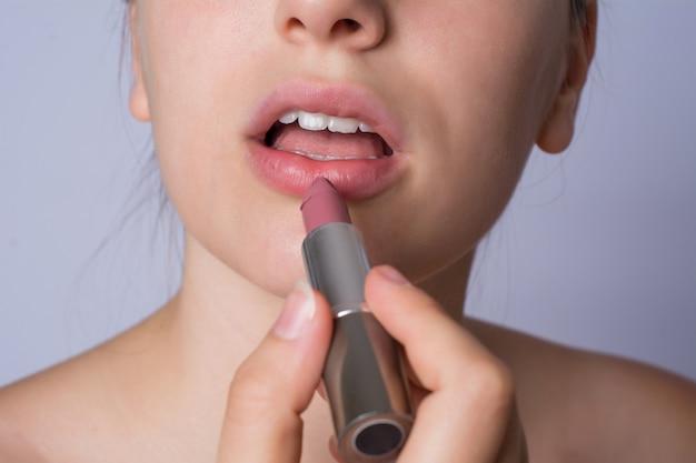 Vrouw die lippenstift toepast.