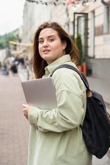 Vrouw die lokaal reist met laptop medium shot
