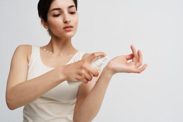 Vrouw die lotion op de hand aanbrengt die de gezondheid van een schone huid hydrateert