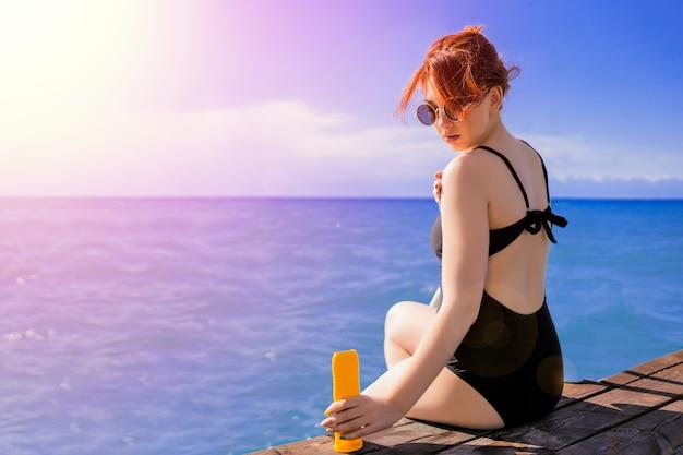 Vrouw die lotion van de zonbescherming toepast.