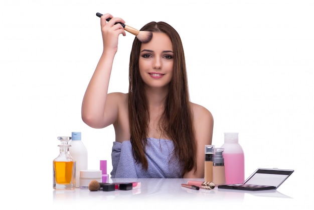 Vrouw die make-up doet die op wit wordt geïsoleerd