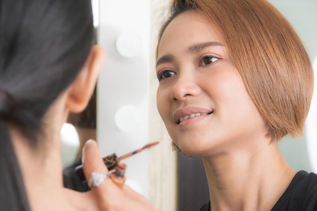 Vrouw die make-up door make-up artiest.