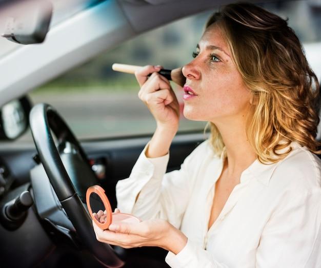 Vrouw die make-up in een auto draagt