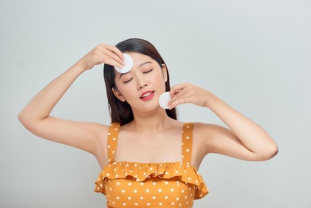 Vrouw die make-up met wattenschijfjes verwijdert