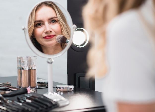 Vrouw die make-up toepast die in spiegel nadenkt