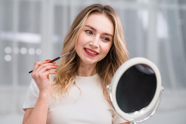 Vrouw die make-up van lippen in spiegel bewondert
