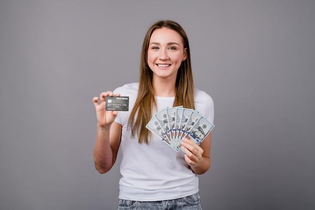 Vrouw die malplaatjecreditcard tonen en het geld van dollarrekeningen dat op grijs wordt geïsoleerd