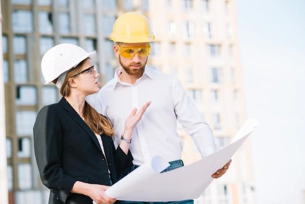 Vrouw die man details van bouwplan verklaart