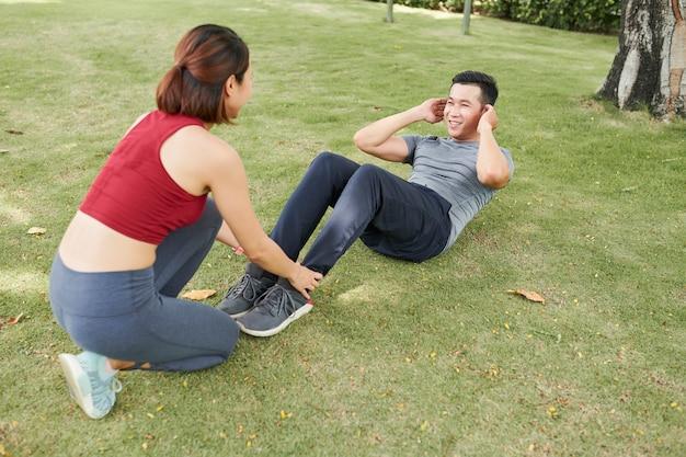 Vrouw die man helpt die crunches doet