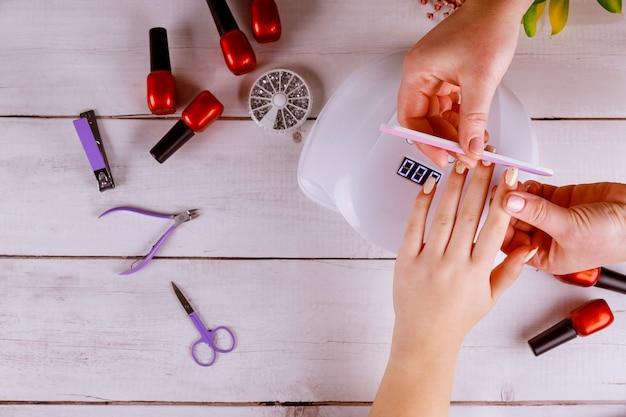 Vrouw die manicure met spijkerraad of nailfile maakt