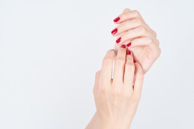 Vrouw die manicureshanden met rood nagellak op wit tonen