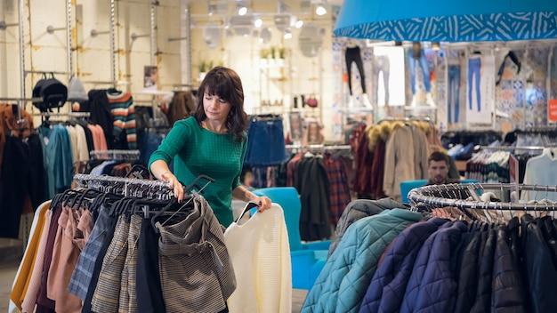 Vrouw die manierkleren in een detailhandel in de stadswandelgalerij kiest, terwijl haar man op haar in de zithoek wacht