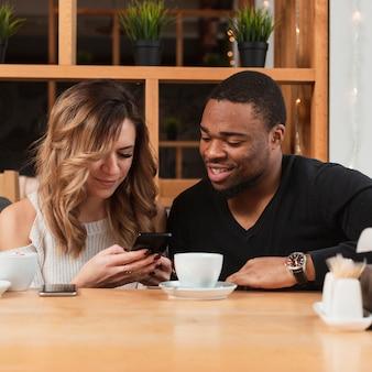 Vrouw die mannetje haar mobiel toont